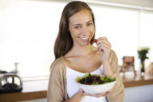 A cropped portrait of a beautiful young woman eating a bowl of salad in her kitchen